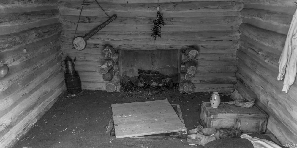 """Featured image for """"The History of BanjoHut.com"""" blog post - black and white photo depicting interior of an old shack with a fireplace, teapot, some shoes on the floor, and an old banjo hanging on the wall."""